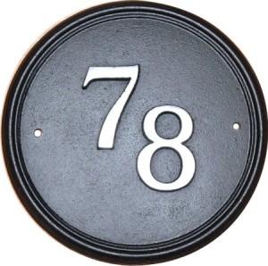 Circular cast iron house number sign.
